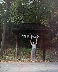 David Eisenhower standing under the sign for Camp David, which his grandfather named after him.