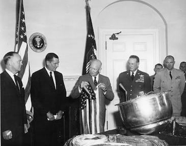 August 15, 1960 - Dwight D. Eisenhower holds the American flag which was carried in the Corona capsule retrieved from Discoverer XIII.